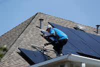 Roland Montoya, lead solar installer with Kosmos Solar, installs solar panels on a home in Arlington on Wednesday.(Rose Baca/Staff Photographer)