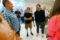"""Michael Orlie (from left) talks to Jeff Bauman and Jake Gyllenhaal  with Keylee Latham, 14, as they tour the Sabolich Prosthetics and Research in Dallas on Tuesday.  In the new movie """"Stronger,"""" Gyllenhaal plays Bauman, a double amputee who survived the Boston Marathon bombing.(Nathan Hunsinger/Staff Photographer)"""
