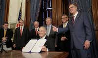 <p><br>Lt. Gov. Dan Patrick, right, gave a thumbs up sign as Gov. Greg Abbott signed an education bill in late May. Second from left was state Education Commissioner Mike Morath. With top leaders, he's making crucial decisions about schools' financial recovery from Hurricane Harvey</p>(Eric Gay/The Associated Press)