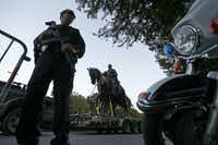 A Dallas Police officer secures an area as a truck carries the Robert E. Lee statue at Robert E. Lee Park on Turtle Creek Boulevard in Dallas, Thursday, Sept. 14, 2017.(Jae S. Lee/Staff Photographer)