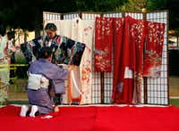 Yuki Takamatsu (standing) is dressed in a kimono by Sumiko Hashimoto during a demonstration at Otsukimi, a moon viewing festival at Klyde Warren Park in Dallas. (2016 file photo)