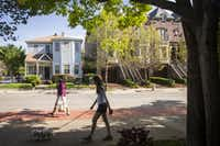 Pedestrians pass the home of Ruth Sanders in Uptown on Saturday, March 26, 2016, in Dallas. Sanders, 93, has Alzheimer's disease. She's being sued by a Dallas real estate firm over a failed deal to sell her house, one of the last historic black homes in Uptown. The home (left) is wedged between a block of new townhomes and a bar across the street. (Smiley N. Pool/The Dallas Morning News)(Smiley N. Pool/Staff Photographer)