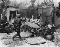 Ron Haberle's photos of My Lai were published in <i>The Cleveland Plain Dealer</i> more than a year after the events of March 16, 1968. Pictured: A soldier burning down a hut in My Lai village. (Ron Haberle courtesy of National Archives)