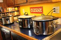 Cheryl Alters Jamison's three slow cookers, lined up and cooking. She borrowed others for testing and evaluation while writing <i>Texas Slow Cooker</i>.(Cathy Barber/Special Contributor)