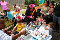 Cassandra Jackson paints the arm of Halston Miller, 5, and Carrie Ray makes balloon animals for Julie Kim (left from balloons) and her family including Mason Wong, 1, Harper Wong, 4, Brynn Cannon, 4, and Ryann Cannon, 2, during the Nextdoor block party in the Belmont Addition in Dallas on Sept. 29.(Nathan Hunsinger/Staff Photographer)