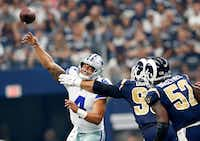 Los Angeles Rams defensive end Aaron Donald (99) gets a hand on Dallas Cowboys quarterback Dak Prescott (4) as he releases a pass during the first half at AT&T Stadium on Sunday.(Tom Fox/Staff Photographer)