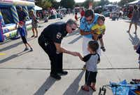Rockwall Police Chief Kirk Riggs met Aaron Gonzalez and his sons, Tanner Gonzalez, 1, and  Carter Gonzalez, 3,  during a National Night Out event at a Home Depot parking lot in Rockwall in 2015.(Michael Ainsworth/Staff Photographer)