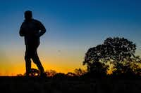 A runner is silhouetted against the sunrise on his early morning workout near Arlington National Cemetery in Arlington, Va., across the Potomac River from the nation's capital. (J. David Ake/The Associated Press)