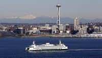 With the Cascade Mountains as a backdrop, a ferry sets sail across Elliott Bay out of Seattle and past the city's iconic Space Needle.(Elaine Thompson/The Associated Press)
