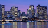 Boston's skyline is illuminated at dusk as it reflects off the waters of Boston Harbor.(Michael Dwyer/The Associated Press)