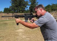 "Shooting instructor Frankie McRae aims an AR-15 rifle fitted with a ""bump stock"" at his 37 PSR Gun Club in Bunnlevel, N.C., on Wednesday. The stock uses the recoil of the semiautomatic rifle to let the finger ""bump"" the trigger, making it different from a fully automatic machine gun, which are illegal for most civilians to own(Allen G. Breed/AP)"