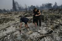 Michael Pond, left, looks through ashes as his wife Kristine, center, gets a hug from Zack Thurston, their daughter's boyfriend, while they search the remains of their home destroyed by fires in Santa Rosa, Calif., Monday, Oct. 9, 2017.(Jeff Chiu/AP)