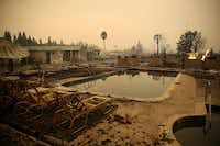 Burned lawn chairs sit next to the swimming pool at the Journey's End Mobile Home Park on October 9, 2017 in Santa Rosa, California. Ten people have died in wildfires that have burned tens of thousands of acres and destroyed over 1,500 homes and businesses in several Northen California counties.(Justin Sullivan/Getty Images)