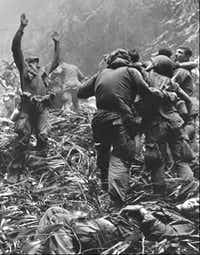 A paratrooper of A Company, 101st Airborne Division, guided a medical evacuation helicopter into a gap in the foliage to pick up soldiers wounded during a patrol into North Vietnamese-controlled territory west of Hue in Vietnam in 1968. (File Photo/The Associated Press)