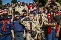 Boy Scouts and Cub Scouts salute during a Memorial Day ceremony in Linden, Mich. The Boy Scouts of America Board of Directors on Wednesday unanimously approved a measure to welcome girls into its Cub Scout program and to deliver a Scouting program to allow older girls to earn the highest rank of Eagle Scout. (The Flint Journal/2017 File Photo)