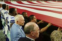 Dallas Cowboys owner Jerry Jones stand locked in arms with players and and other team personnel during the playing of the national anthem before their game against the Arizona Cardinals on Sept. 25 at University of Phoenix Stadium in Glendale, Ariz.(Staff Photographer/Andy Jacobsohn)