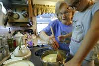 Peggy Garmon shows her granddaughter Summer Garmon, 6, the proper technique to stir fudge.(Nathan Hunsinger/Staff Photographer)