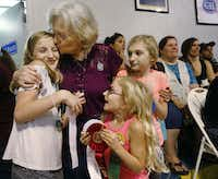Allyson Garmon, 11, (left) is kissed by her grandmother Peggy Garmon with her sisters Summer (bottom) and Elizabeth, 11, after winning one of the cooking contests at the State Fair of Texas.(Nathan Hunsinger/Staff Photographer)