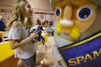 Allyson Garmon, 11, laughs with the Spam mascot, Sir Can-A-Lot, after winning the Kid Chef Spam cooking contest.(Nathan Hunsinger/Staff Photographer)