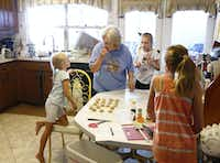 Summer Garmon, 6, (from left) looks at her grandmother Peggy Garmon with her sisters Elizabeth and Allyson, both 11, make candy at Peggy's home in Rowlett.(Nathan Hunsinger/Staff Photographer)