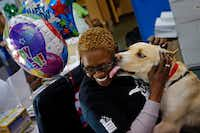 In this 2016 file photo, Teri Williams, an employee of Dallas Animal Services, is licked by Titan as he prepares to leave with his adoptive owners.(G.J. McCarthy/Staff Photographer)