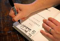 Olson autographs a copy of&nbsp;<i>The Sandcastle Empire</i>&nbsp;for a fan and fellow writer, Jennifer Judd, at West Oak Coffee Bar in Denton.&nbsp;(Jae S. Lee/Staff Photographer)