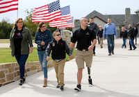 The Byers family (from left): Megan, Cameron, Preston, U.S. Air Force Sr. Airman (Ret.) Brandon Byers make their way to the front door of their new smart home Tuesday in McKinney. The home was built as part of the R.I.S.E. program through the Gary Sinise Foundation, which builds specially adapted smart homes for severely wounded veterans nationwide.(Vernon Bryant/Staff Photographer)