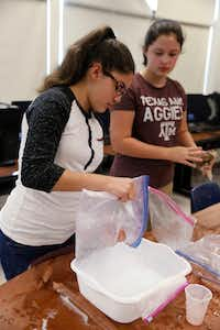 Paige Aleman (left) and Nora Allender cleaned up after making homemade ice cream in a STEM class at Dallas ISD's Robert T. Hill Middle School last May.(Ron Baselice/Staff Photographer)