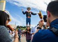Fairgoers eat Fletcher's Corny Dogs while taking photos of Big Tex on Wednesday, October 4, 2017 at the State Fair of Texas in Dallas.(Ashley Landis/Staff Photographer)