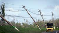 Power poles lean precariously along Highway 118 near San Isidro, Puerto Rico. About 86 percent of the island still doesn't have power about a month after Hurricane Maria struck.(Jose A. Iglesias/Miami Herald)