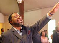 Pastor Andre Byrd Sr. of New Covenant Christian Fellowship Church raises his hand in praise during Sunday service. He will accompany the church's choir to Europe to perform in three cities in Spain later this month.(Ron Baselice/Staff Photographer)