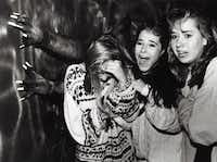 <p>Sixteen-year-olds Natalie Monzingo, Kristina Hughes and Lora Moss scream as they walk through the March of Dimes Haunted House on Oct.  21, 1988.</p>(File Photo/David Woo)