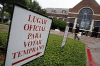 A sign in Spanish points toward City Hall in Farmers Branch, indicating an early voting location.(File Photo/Staff)