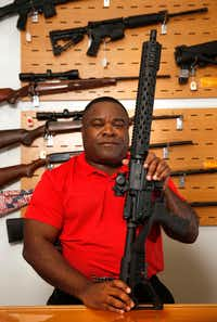 Michael Cargill, Central Texas Gun Works owner poses with an AR-15 with a bump stock attached in his store in Austin, Texas on Thursday, October 19, 2017.(Vernon Bryant/Staff Photographer)