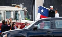 President Donald Trump holds up a Texas flag after attending a briefing from federal, state and local organizations after Hurricane Harvey at Annaville Fire Station 5 in Corpus Christi on Aug. 29, 2017.(Nathan Hunsinger/Staff Photographer)