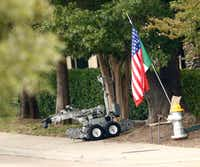 A suspicious package is pulled out of the bushes by a police robot in front of the Southwestern Women's Surgery Center on Greenville Avenue in northeast Dallas.(Nathan Hunsinger/Staff Photographer)