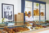 Baker Clint Cooper stands behind the counter at Boulangerie by Village Baking Co., which is still open on Lower Greenville.(Kevin Marple)