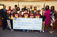 DeSoto school district board members and officials, including Debbye Garner (right), celebrate receiving a $15 million check with students from Woodridge Elementary.(DeSoto ISD)