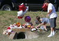 "<p>Miley Grahmann, 8, left a bear with a jar of lip balm (in case her lips get chapped in heaven) on Monday near  where the body of a small child was found Sunday morning. Miley was with <span style=""font-size: 1em; background-color: transparent;"">her father, Patrick Grahmann.</span></p>(Nathan Hunsinger/Staff Photographer)"
