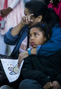 Diana Delgado wipes away a tear as she holds her crying grandson Lejohn Rogers, 7, during a vigil at a memorial Sunday for Sherin Mathews.(Ashley Landis/Staff Photographer)