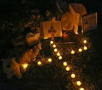 Artificial candles placed in the pattern of a cross light a small tribute set up for Sherin Mathews on Oct. 12.(Ron Baselice/Staff Photographer)