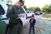 A Border Patrol agent reads the birth certificate of Alejandro, 8. The certificate was the only thing he brought with him as he and others crossed the Rio Grande near McAllen. (2014 File Photo/The New York Times)