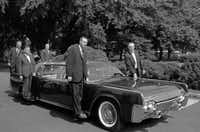 In June, 1961, U.S. Secret Service agents pose on retractable stands on President John F. Kennedy's new plastic-topped Lincoln Continental limousine outside the White House, after its delivery in Washington.  The car has three roof combinations, a rear seat that can be raised and lowered, retractable foot stands for Secret Service men, two two-way radio telephones, and a master control panel for power accessories. (Henry Burroughs/AP)