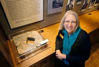 "University archivist Betty Shankle poses next to a broken marble marker with the inscription ""Carlisle Military Academy 1906"" in the University of Texas at Arlington Special Collections in the university library.(Tom Fox/Staff Photographer)"