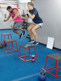 Thomas Karam (left) and Sam Nelson at the box jump station during a high intensity workout at Fit Body Boot Camp in Dallas.(Ron Baselice/Staff Photographer)