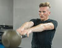 Troy Smits swings a kettlebell during a high intensity workout.(Ron Baselice/Staff Photographer)
