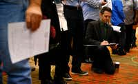 Brady Snowden fills out forms while in line during the You're Hired Job Fest at the Sheraton Dallas Hotel on Thursday.(Nathan Hunsinger/Staff Photographer)