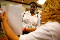 Eboni Parker talks to LeeAnn Stanley with Workforce Solutions Greater Dallas during the You're Hired Job Fest on Thursday.(Nathan Hunsinger/Staff Photographer)