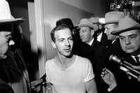 In this Nov. 23, 1963, file photo, surrounded by detectives, Lee Harvey Oswald talks to the media as he is led down a corridor of the Dallas police station. (AP Photo)(AP)
