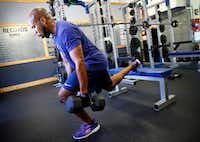 Donovan Lewis uses dumbbells while doing Bulgarian split squats.(Tom Fox/Staff Photographer)